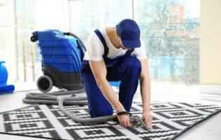 Dieses Foto zeigt einen Angestellten bei der Reinigung eines Teppichs.